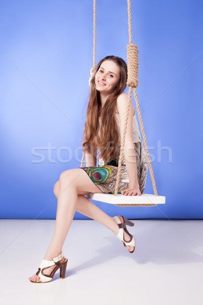 Młodych uśmiechnięta kobieta sukienka posiedzenia huśtawka portret Zdjęcia stock © julenochek