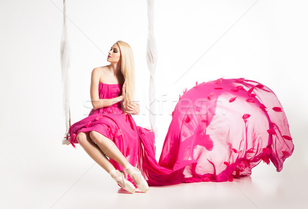 Portrait of beautiful blonde girl on swing in bright pink dress Stock photo © julenochek