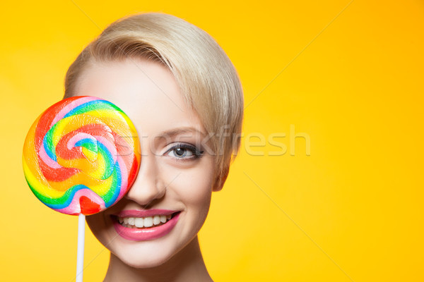 Cheerful blondie with lollipop covering eye Stock photo © julenochek