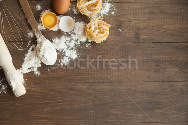 Cuisine composition with fettuccine cracked eggs,kitchenware, flour. Stock photo © julenochek