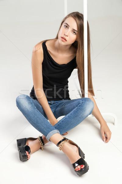 Beautiful stylish model sitting near clothes rack Stock photo © julenochek