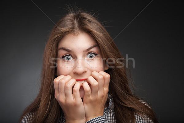 Amazed woman biting nails. Stock photo © julenochek