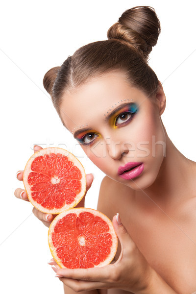 Close-up of young woman with make-up holding cut grapefruit Stock photo © julenochek