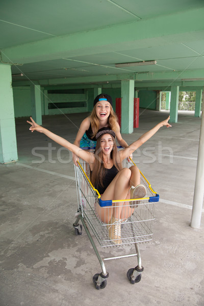 Two cheerful girl have fun riding in shopping cart Stock photo © julenochek