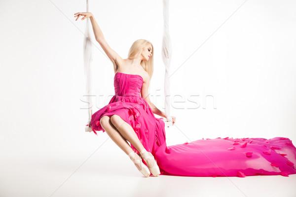 Portrait of beautiful blonde girl on swing in bright pink dress Stock photo © julenochek