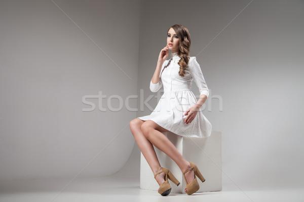 young brunette in white dress sitting in studio Stock photo © julenochek