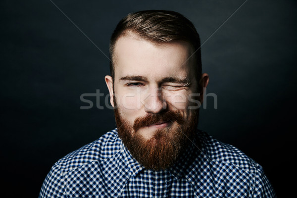 Winking red bearded man studio portrait on dark background Stock photo © julenochek