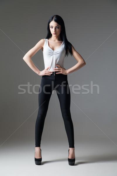 Slim black-haired woman posing on high heels Stock photo © julenochek