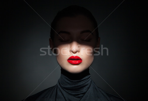Beautiful model with bright red lips and face half covered in shadow Stock photo © julenochek