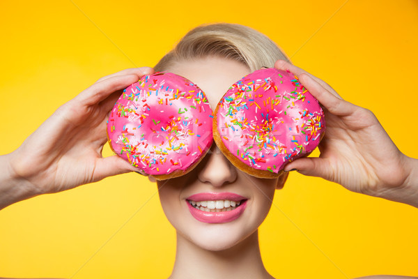 Short-haired model covering eyes behind two pink donuts Stock photo © julenochek