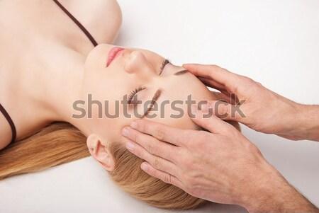 Young woman receiving a head massage on white Stock photo © julenochek