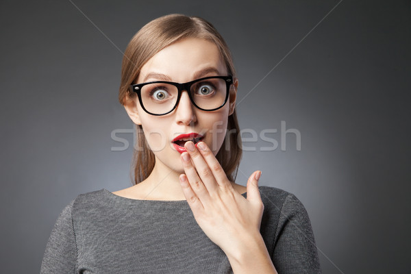 Wide-eyed astonished woman covering mouth with hand Stock photo © julenochek