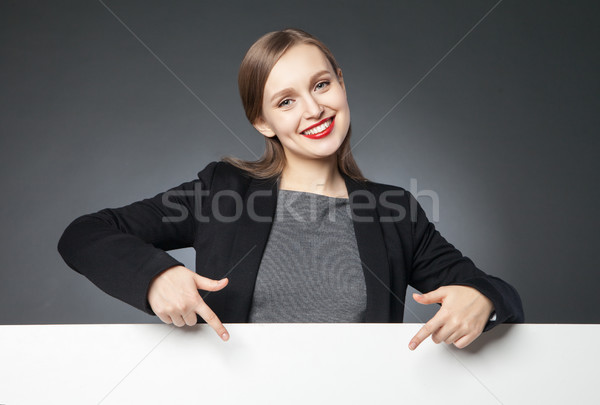 Smiling beautiful woman pointing at blank space Stock photo © julenochek