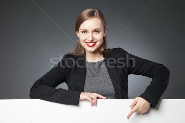 Smiling beautiful woman pointing at blank space Stock photo © julenochek