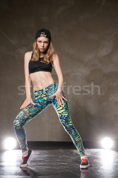 Stylish dancer posing against of brown wall and lights Stock photo © julenochek