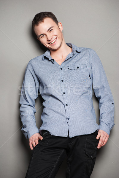Smiling man casually leaning against the wall Stock photo © julenochek