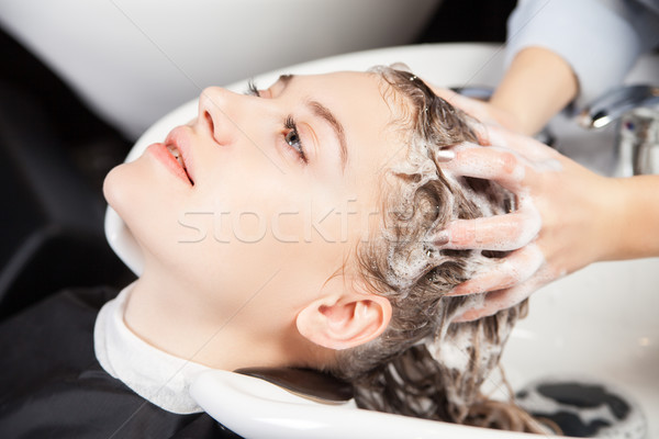 Woman washing head in hairdressing saloon Stock photo © julenochek