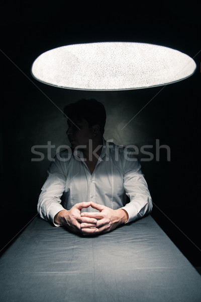 Stock photo: Man in a dark room illuminated only by lamp
