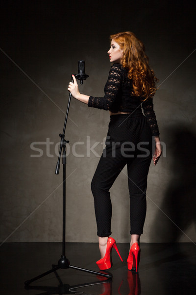 Stock photo: Portrait of beautiful singer in red heels and black clothes