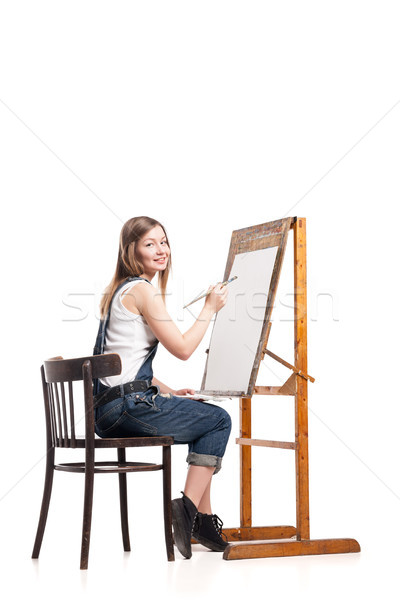 Young smiling woman painter with paintbrush standing at easel  Stock photo © julenochek