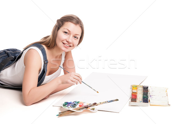 Young woman happily lies  on the floor drawing in her note pad Stock photo © julenochek