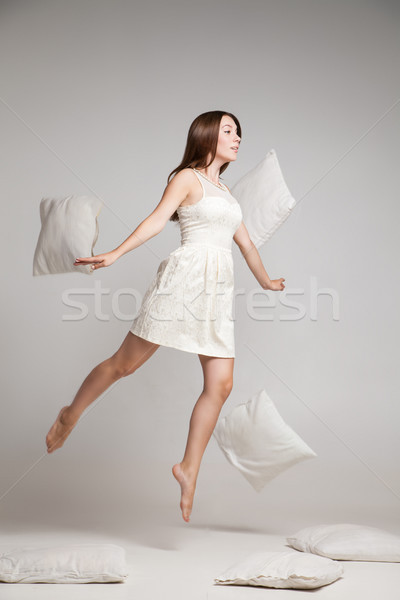 Woman in white dress in mid air with flying pillows Stock photo © julenochek
