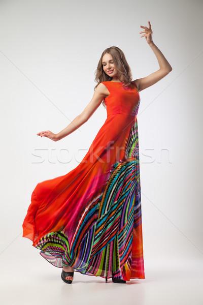 Beautiful young woman in bright colorful dress dancing Stock photo © julenochek