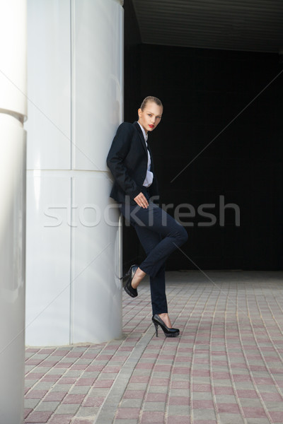 Vonzó nő öltöny pózol fehér oszlop portré Stock fotó © julenochek