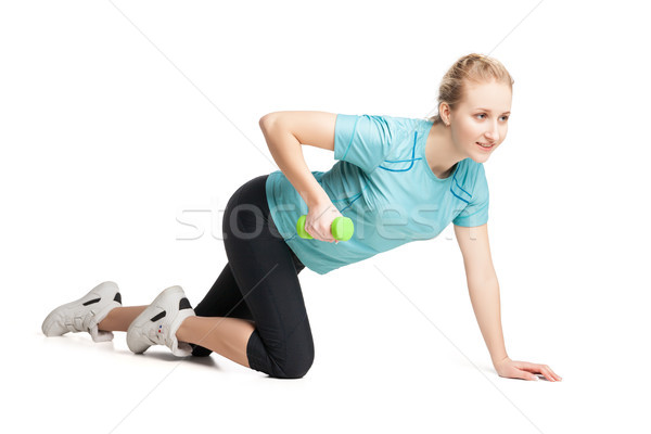Stock photo: Athletic young woman works out with green dumbbells