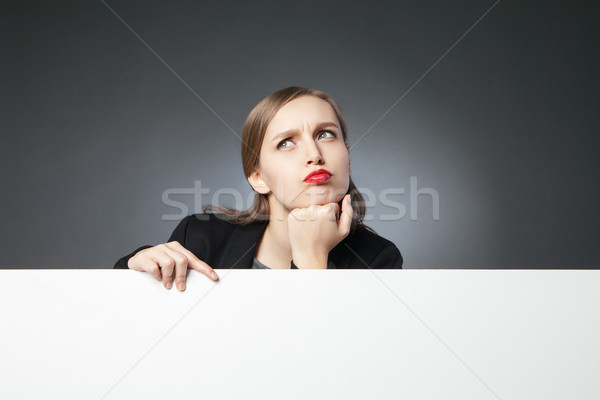 Puzzled businesswoman looking up Stock photo © julenochek