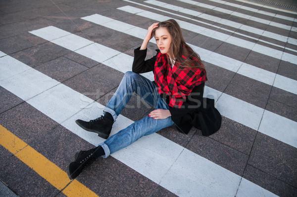 Portrait of brunette in stylish coat sitting on crosswalk Stock photo © julenochek