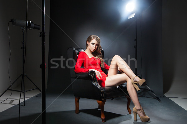 Seductive model in red dress in spotlight Stock photo © julenochek