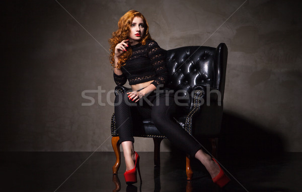 Model in high heels sitting on black chair Stock photo © julenochek