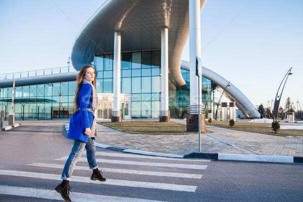 Side view of brunette in blue coat jumping on crosswalk Stock photo © julenochek