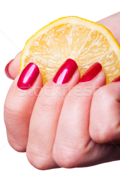 Hand with manicured nails squeeze lemon on white Stock photo © juniart