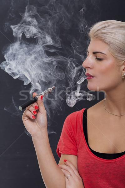 Stylish blond woman smoking an e-cigarette Stock photo © juniart