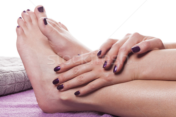 Stock photo: Manicured hands stroke bare feet with nail polish