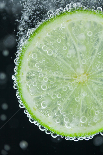 Lime slice falling into water Stock photo © juniart
