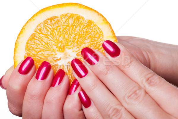Hand with manicured nails touch an orange on white Stock photo © juniart