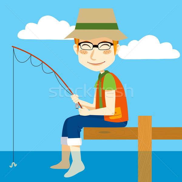 Szczęśliwy rybak człowiek posiedzenia dok wędka Zdjęcia stock © Kakigori
