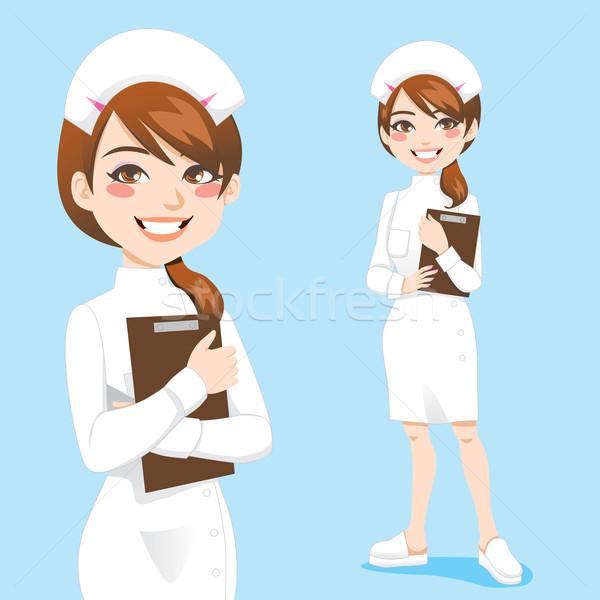 Hermosa enfermera amistoso sonriendo portapapeles Foto stock © Kakigori