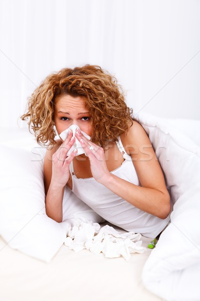 Stock photo: Sick woman blowing her nose