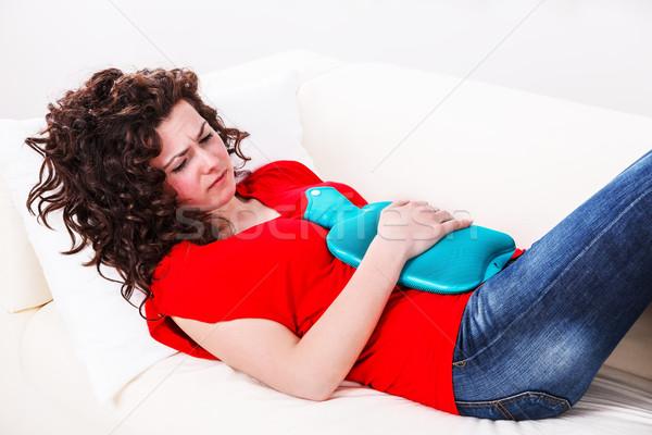 Menina dor de estômago sofá mulher mão casa Foto stock © kalozzolak