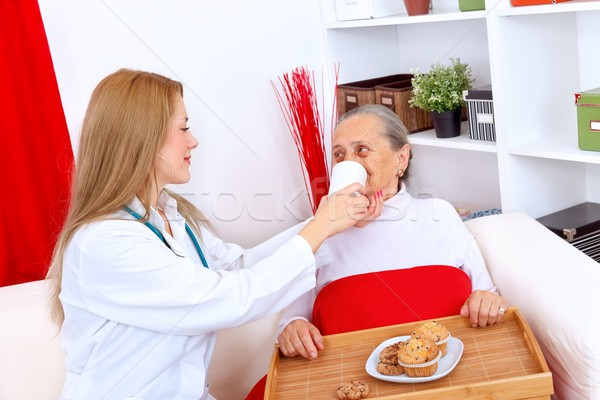 Nurse helping elderly woman Stock photo © kalozzolak