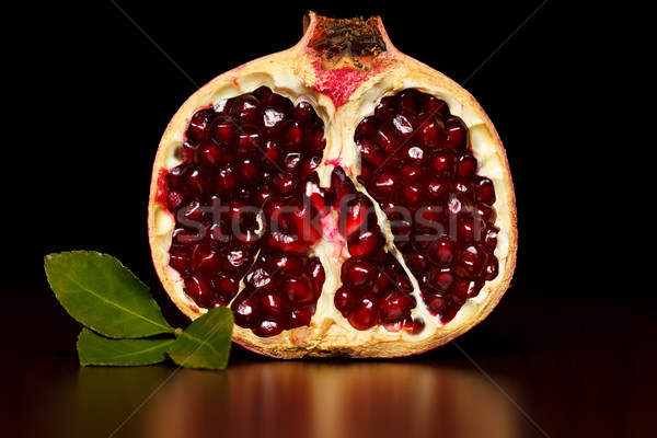 Half-cutted pomegranate with green leaf Stock photo © kalozzolak