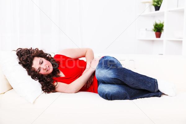 Menina sofá dor de estômago mulher mão casa Foto stock © kalozzolak