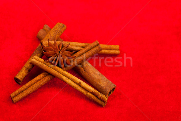 Cinnamon sticks and star anise on red Stock photo © kalozzolak