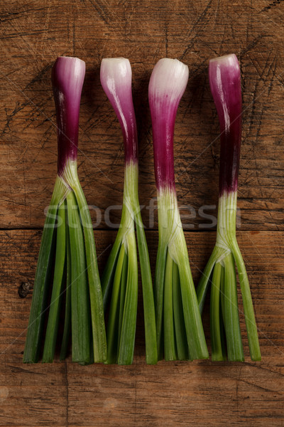 Four green onions on wooden table Stock photo © kalozzolak