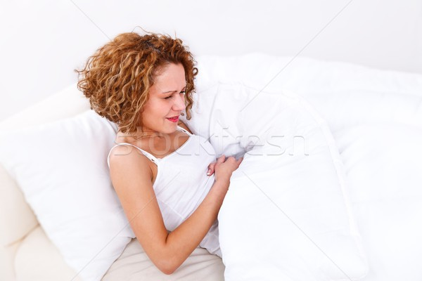 Dor de estômago mulher cama menina jovem feminino Foto stock © kalozzolak