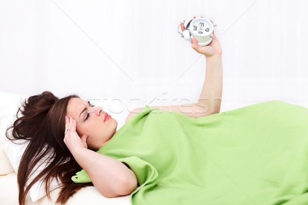 álmos nő ágy ébresztőóra kéz lány Stock fotó © kalozzolak